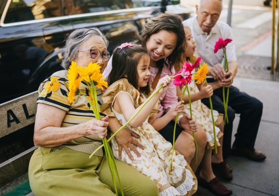 Three generations of a family sitting together on a bench holding brightly colored flowers.